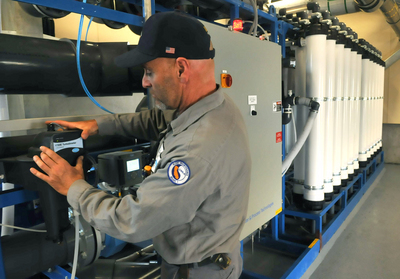 Gary Wettstein checks a control panel on a new filtration unit
