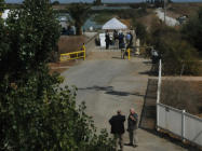People walk along a levee between diked baylands as they gather