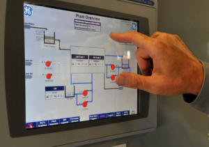 Gary Wettstein checks a process logic control panel on a new filtration unit